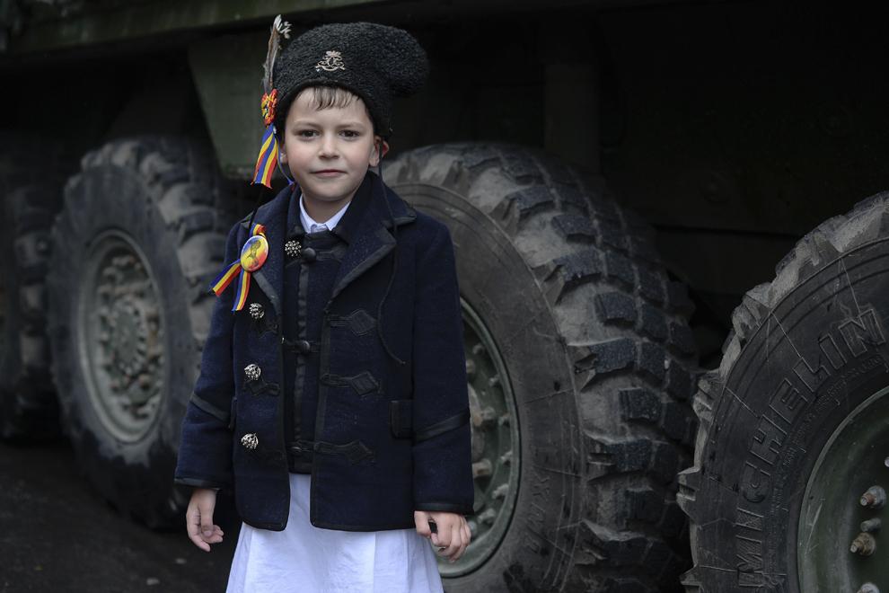 """Alex, 6 ani, îmbrăcat cu un costum de june, pozează lîngă un transportor militar blindat """"Stryker"""" parcat pe Bulevardul Ferdinand din Sinaia, în timpul evenimentului """"Marşul Cavaleriei"""", joi, 14 mai 2015."""