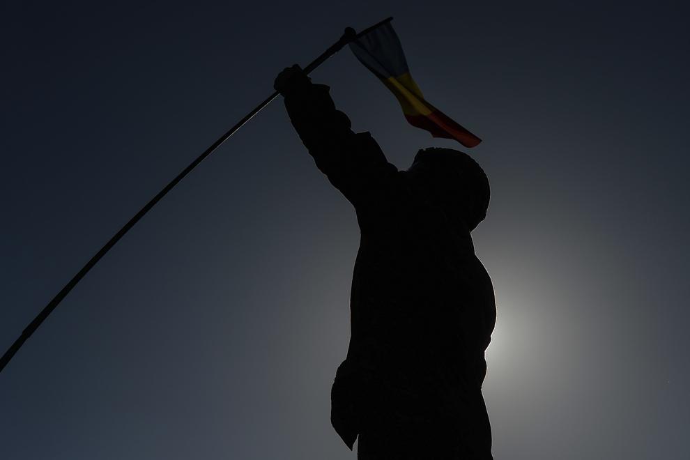 """Caporalul Livingood prinde drapelul României pe antena unui transportor militar blindat """"Stryker"""", în baza militară Mihail Kogalniceanu, miercuri, 13 mai 2015."""