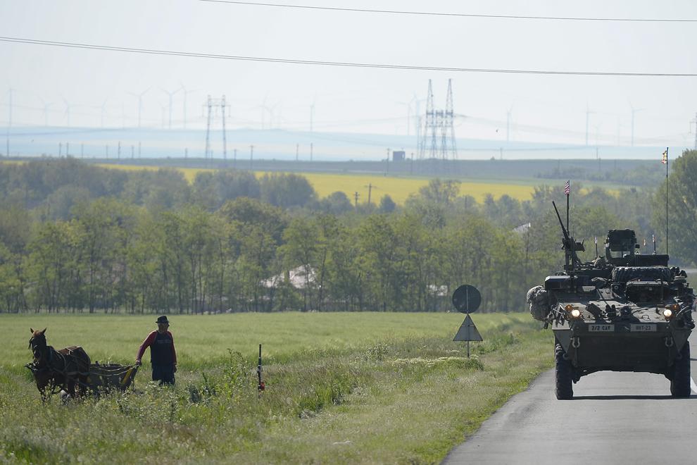 """Un bărbat aflat lângă căruţa sa priveşte un transportor militar blindat """"Stryker"""" în timpul deplasării acestuia prin judeţul Constanţa, miercuri, 13 mai 2015."""