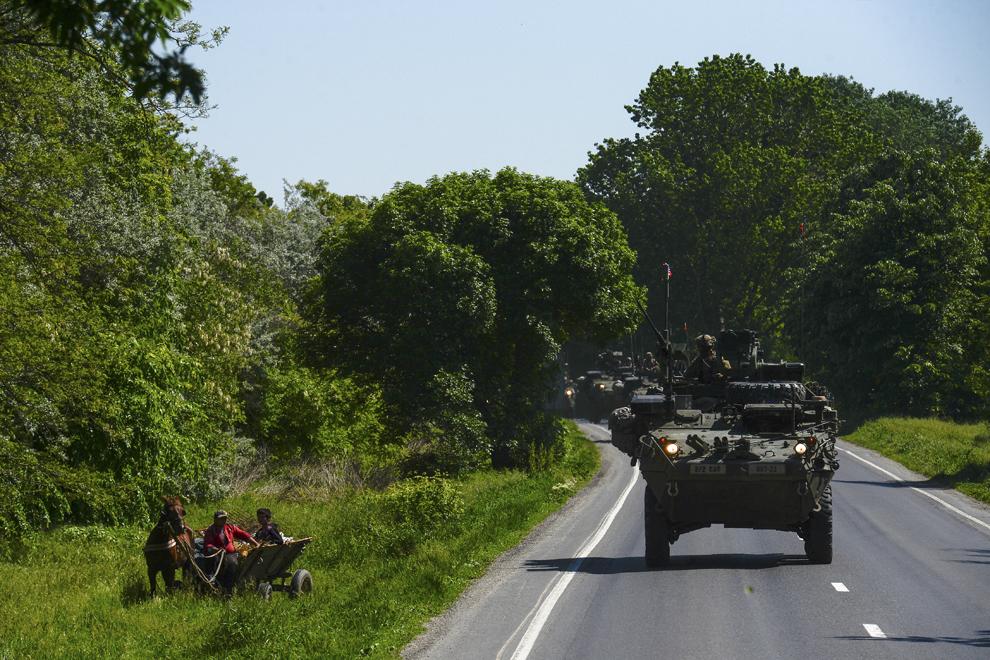 """Persoane aflate într-o căruţă privesc un transportor militar blindat """"Stryker"""" în timpul deplasării acestuia prin judeţul Ialomiţa, miercuri, 13 mai 2015."""