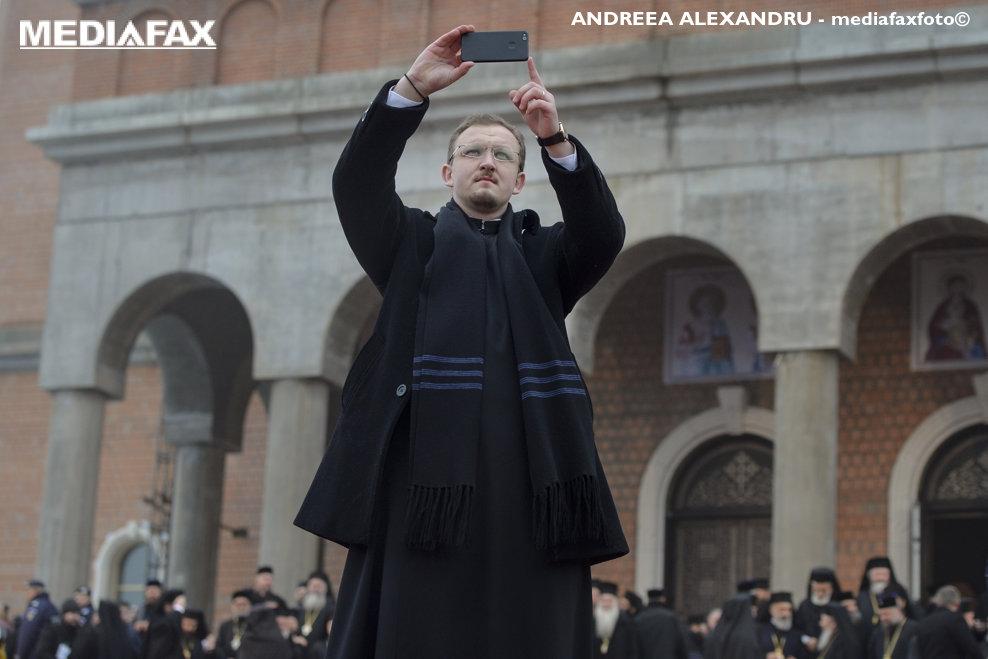 Un preot fotografiza adunarea miilor de credinciosi la ceremoniile de sfintire a altarului Catedralei Manturii Neamului, duminica 25 noiembrie 2015, in Bucuresti.