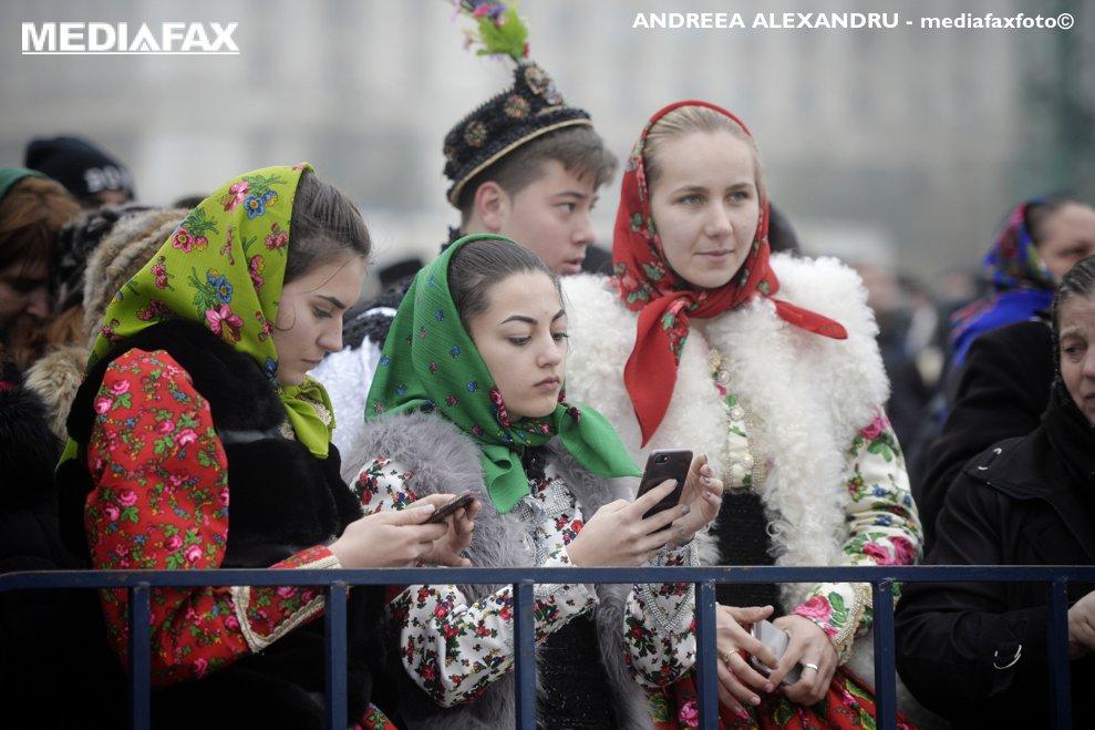 Doua tinere imbracate in costume populare traditionale isi verifica telefoanele mobile in apropierea Catedralei Mantuirii Neamului, in timpul slujbei de sfintire a altarului lacasului de cult, duminica 25 noiembrie 2018, in Bucuresti.