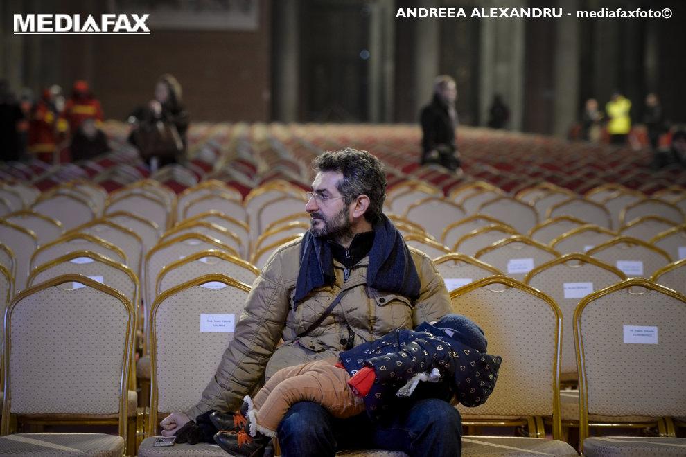 Un barbat isi tine in brate copilul adormit, in incinta Catedralei Mantuirii Neamului, dupa sfintirea altarului lacasului de cult, duminica 25 noiembrie 2015, in Bucuresti.