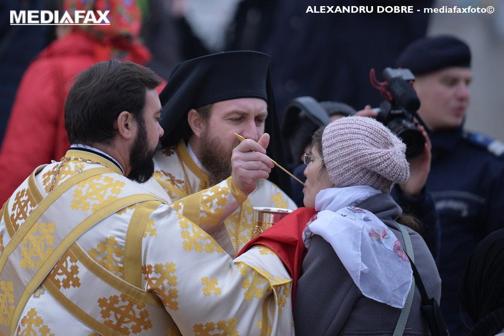O credincioasa primeste impartasania de la preoti, la finalul cermoniilor de sfintire a altarului Catedralei Mantuirii Neamului,  duminica 25 noiembrie 2015, in Bucuresti.