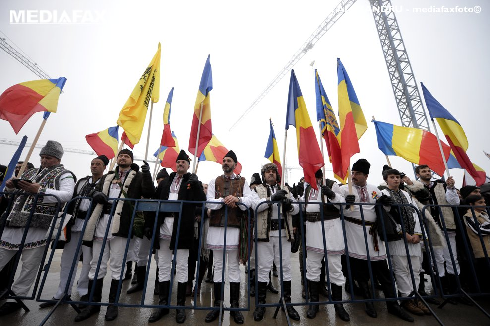 Persoane imbrcate in costume traditionale si purtand steaguri tricolore asteapta la Catedrala Mantuirii Neamului, inceperea slujbei de sfintire a altarului lacasului de cult, duminica 25 noiembrie 2018, in Bucuresti.
