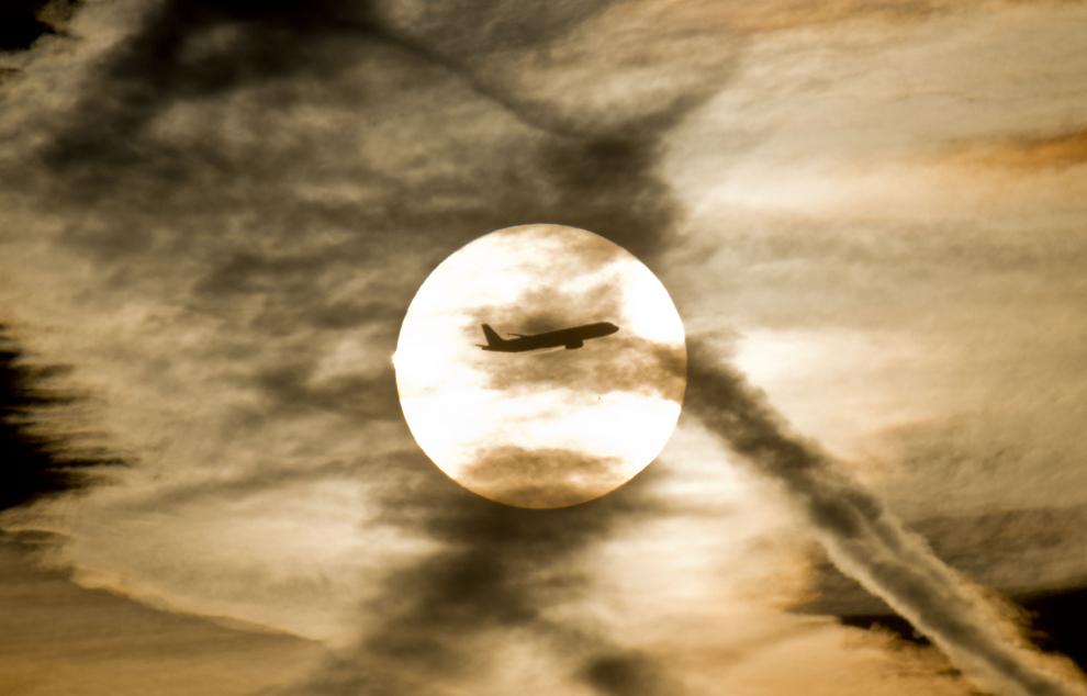 Un avion care se pregăteşte să aterizeze pe aeroportul din Frankfurt pe Main, zboară pe fundalul soarelui care tocmai răsare, marţi, 22 noiembrie 2011.