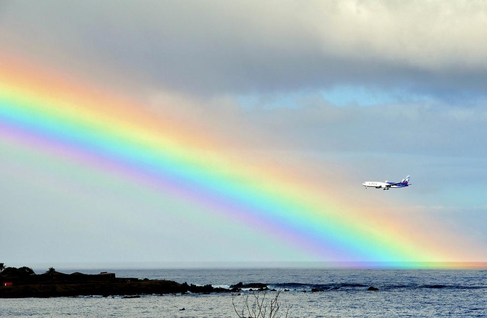 Un avion poate fi văzut lânga un curcubeu, deasupra golfului Ankaroa, în Insula paştelui, în Oceanul Pacific, la 3700 km depărtare de coastele chiliene, luni, 12 iulie 2012.