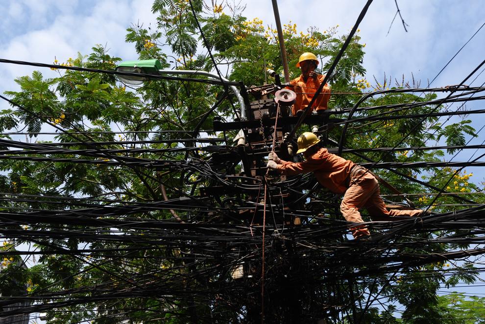 Doi muncitori repară cablurile aflate în vârful unui stâlp de electricitate, în Hanoi, joi, 14 iunie 2012. Guvernul vietnamez şi-a exprimat ambiţia de a construi în centrul ţării prima centrală nucleară.