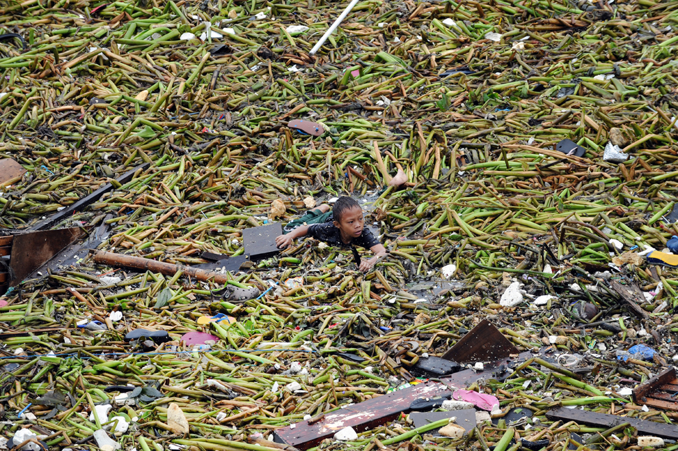 Un băiat înoată printre resturi în timp ce încearcă să-şi salveze bunurile după ce două barje au lovit o zonă de locuinţe improvizate, în Manila, luni, 30 iulie 2012.
