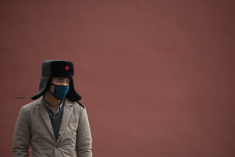 Un bărbat purtând o mască pe faţă stă lângă un perete din interiorul Oraşului Interzis, în timpul unei zile cu o atmosferă extrem de poluată, cauzată de o furtună de nisip, în Beijing, joi, 28 februarie 2013.