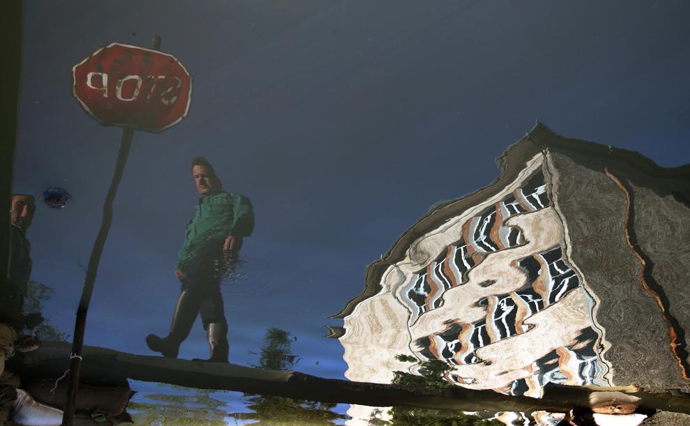 Imaginea unui bărbat se reflectă pe o stradă inundată din oraşul Nicopole, în nordul Bulgariei, sâmbătă, 15 aprilie 2006.