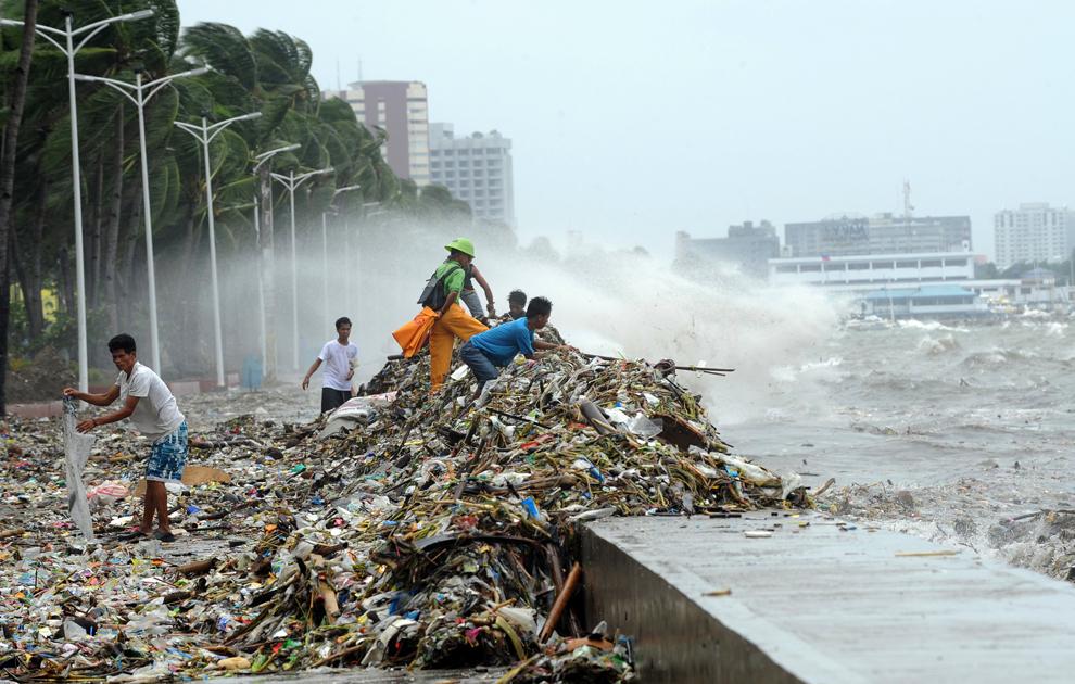 Mai mulţi oameni colectează materiale reciclabile din gunoaiele aruncate de valuri pe faleza Roxas din Manila, în timp ce ploile torenţiale şi vânturile puternice aduse de taifunul Saola lovesc capitala Filipinelor pentru a doua zi, miercuri, 1 august 2012.