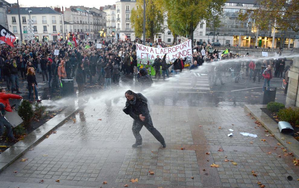 Un manifestant este stropit cu apă in timpul unei protest împotriva unui proiect de a construi un aeroport internaţional în Notre-Dame-des-Landes, lângă Nantes, în faţa Prefecturii din Loire-Atlantique, sâmbătă, 24 noiembrie 2012.