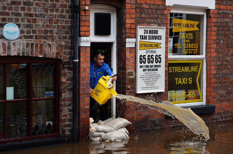 Un bărbat foloseşte o găleată pentru a scoate apa dintr-un dispecerat de taxi, în timp ce nivelul apei continuă să crească pe râul Ouse ca urmare a ploilor torenţiale din York, în nordul Angliei, miercuri, 26 septembrie 2012.