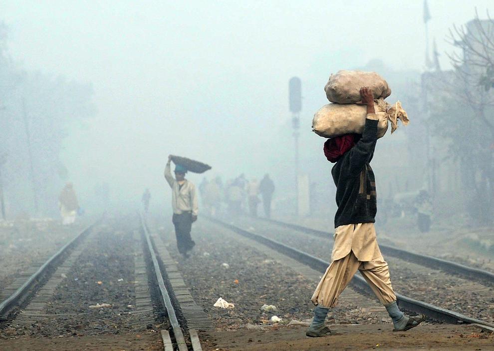 Muncitori pakistanezi traversează  prin ceaţă o cale ferată din Lahore, joi, 5 ianuarie 2012. Ceaţa a continuat să persiste în cea mai mare parte a Punjabului, inclusiv in Lahore, conducând la perturbarea sistemului de comunicaţii din zonă.