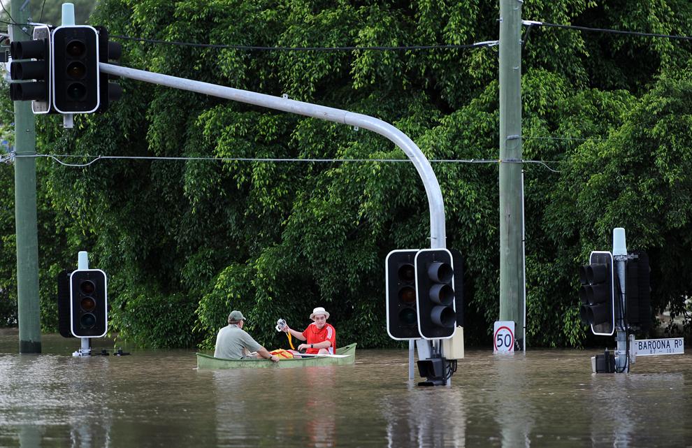 Locuitorii unei periferii a oraşului Brisbane din Australia folosesc o barcă pentru a naviga prin oraşul inundat, în timp ce nivelul apelor continuă să crească, miercuri, 12 ianuarie 2011. Al treilea oraş ca mărime al Australiei suferă de pe urma celor mai mari inundaţii din ultimul secol, care ameninţă peste 20.000 de case şi care au provocat 25 de decese.