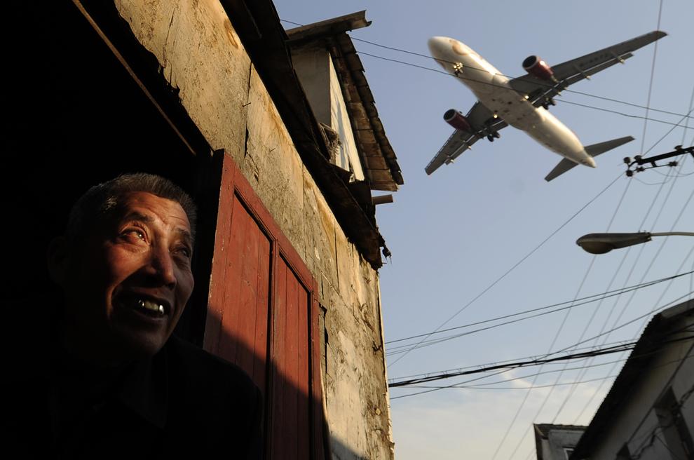 Un bărbat urmăreşte un avion de linie care zboară pe deasupra casei sale, în apropierea aeroportului internaţional Hongqiao din Shanghai, joi, 5 ianuarie 2012. Un grup care reprezintă interesele companiile aeriene chineze a declarat ca acestea nu vor plăti taxa pe emisii de carbon impusă de Euniunea Europeană începând cu 1 ianuarie.