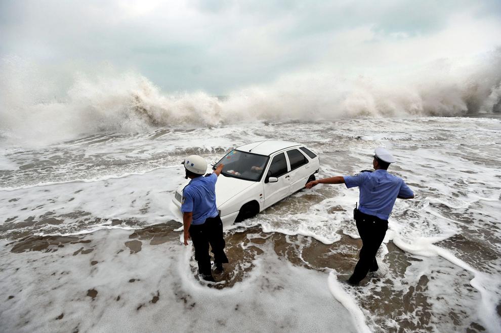 O fotografie realizată pe 28 august 2012 înfăţişează doi poliţişti care încearcă să ajute la salvarea unei maşini înconjurată de apă după ce proprietarul a parcat-o pe ţărm pentru a urmări valurile aduse de taifunul Bolaven, în Qingdao, în provincia Shandong din nord-estul Chinei.