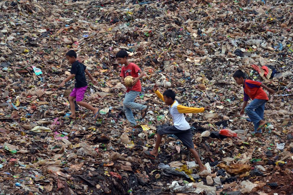 Copii aleargă peste mormane de deşeuri, înainte de a juca un meci de fotbal, la o groapă de gunoi din Bantar Gebang, în Indonezia, sâmbătă, 30 martie 2013.