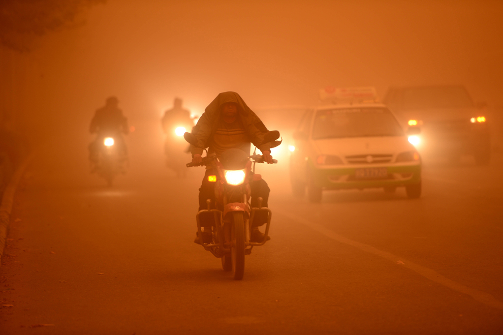 Mai mulţi motociclişti conduc cu luminile aprinse în timpul unei furtuni de nisip puternice, în provincia Yecheng din Regiunea Autonomă Uigură, în nord-estul Chinei, marţi, 16 aprilie 2013.