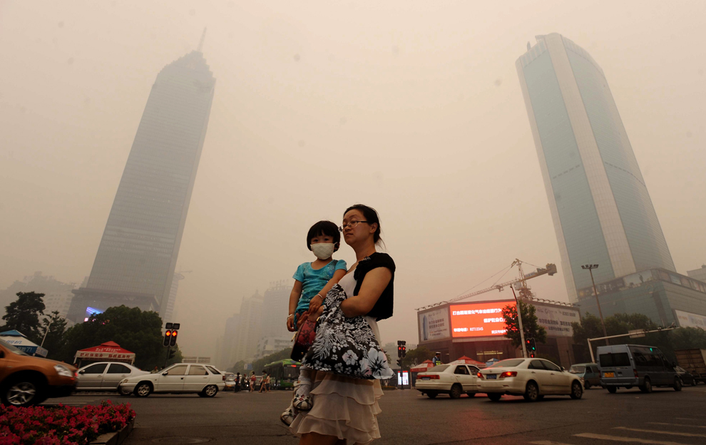 O femeie îşi ţine în braţe fiica, care poartă o mască, în timp ce se îndreaptă spre o intersecţie aglomerată din Wuhan, în provincia chineză Hubei, joi, 11 iunie 2012. Metropola chineză Wuhan a fost acoperită de o ceaţă galbenă şi deasă, provocând îngrijorare în rândul celor 9 milioane de locuitori.