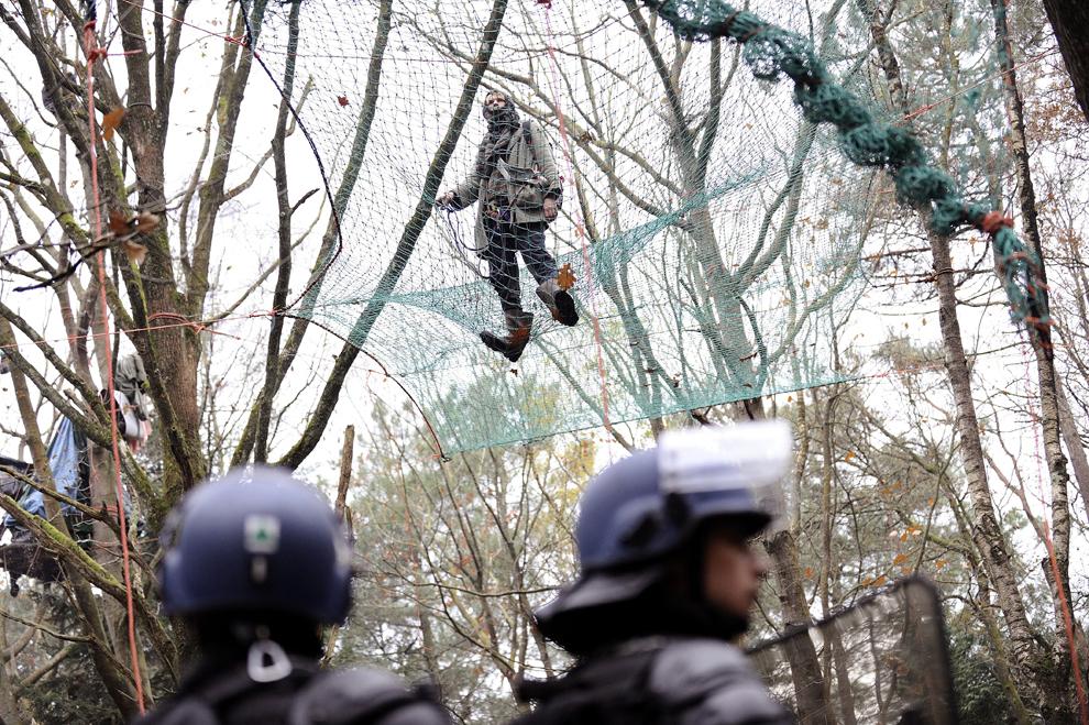 Un tânăr protestează pe o plasă legată de mai mulţi copaci, în faţa scutierilor francezi, împotriva deciziei primului ministru francez Jean-Marc Ayrault de a construi un nou aeroport pe locul unei mlaştini protejate, în Notre-Dame-des-Landes, sâmbătă, 24 noiembrie 2012.
