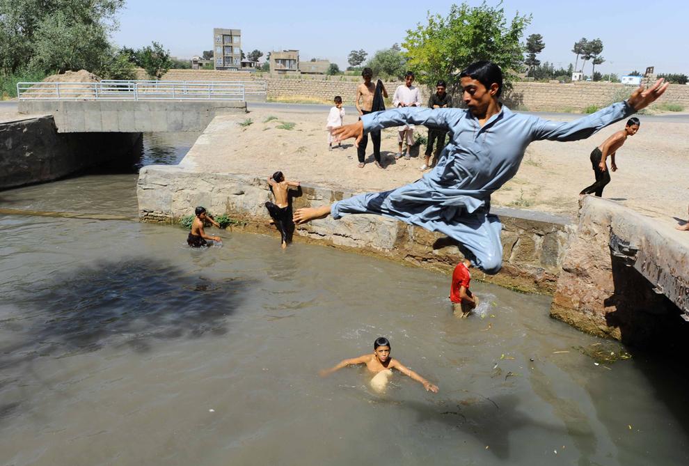 Tineri afgani sar într-un râu din Herat, Afganistan, luni, 29 iulie 2013.