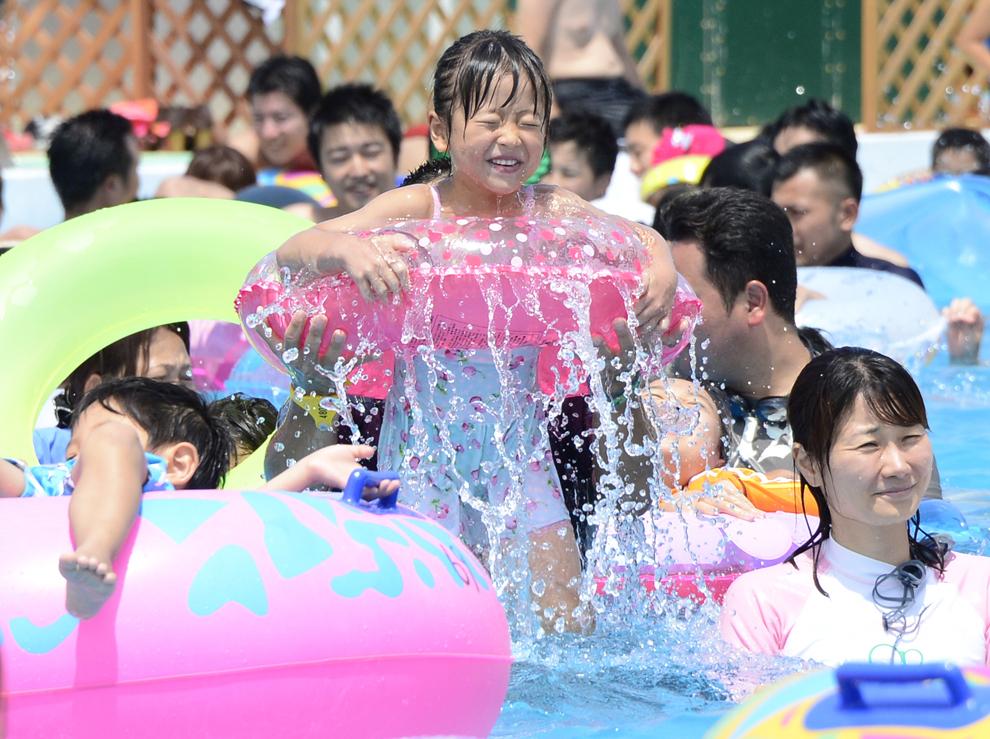 O fetiţă reacţionează în timp ce face baie într-o piscină suprapopulată din parcul de distracţii Toshimaen din Tokio, Japonia, duminică, 29 iulie 2013.