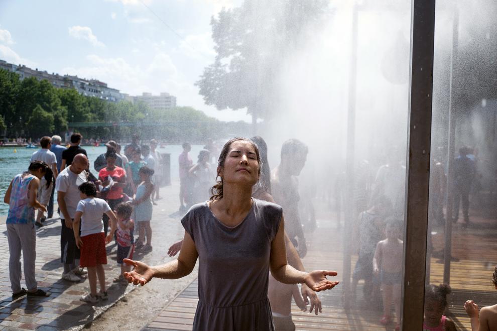 O femeie stă sub o instalaţie ce pulverizează apă, în Paris, duminică, 21 iulie 2013.