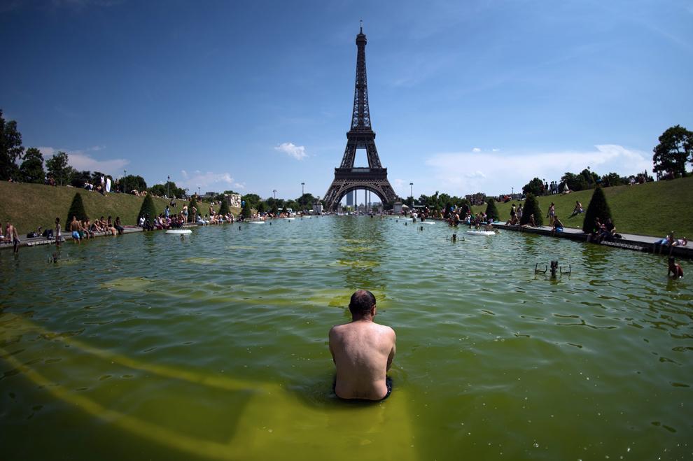Un bărbat se relaxează în apa unei fântâni, lângă Trocadero, în Paris, Franţa, luni, 22 iulie 2013.