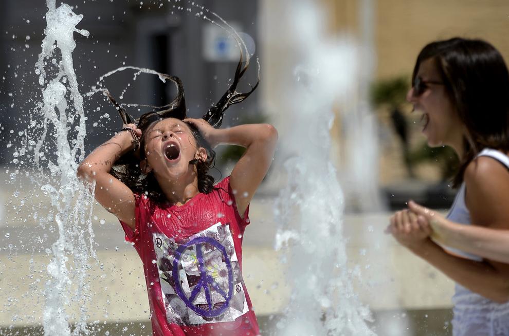 O turistă se răcoreşte în fântâna creată de Ara Pacis în Roma, Italia, sâmbătă, 27 iulie 2013.