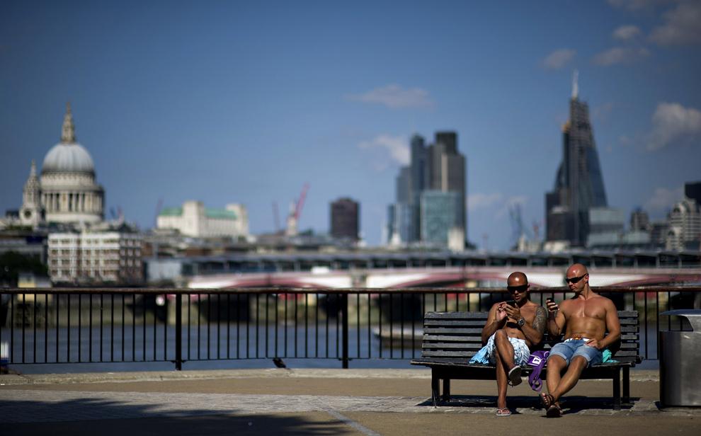 Doi bărbaţi stau la plaja pe o bancă, în South Bank, Londra, 18 iulie 2013.