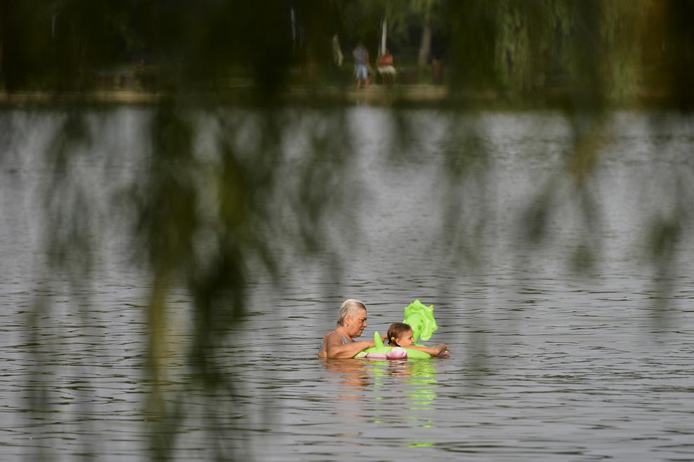 O fetiţă înoată alături de bunica sa, în lacul din parcul I.O.R din Bucureşti, luni, 29 iulie 2013.