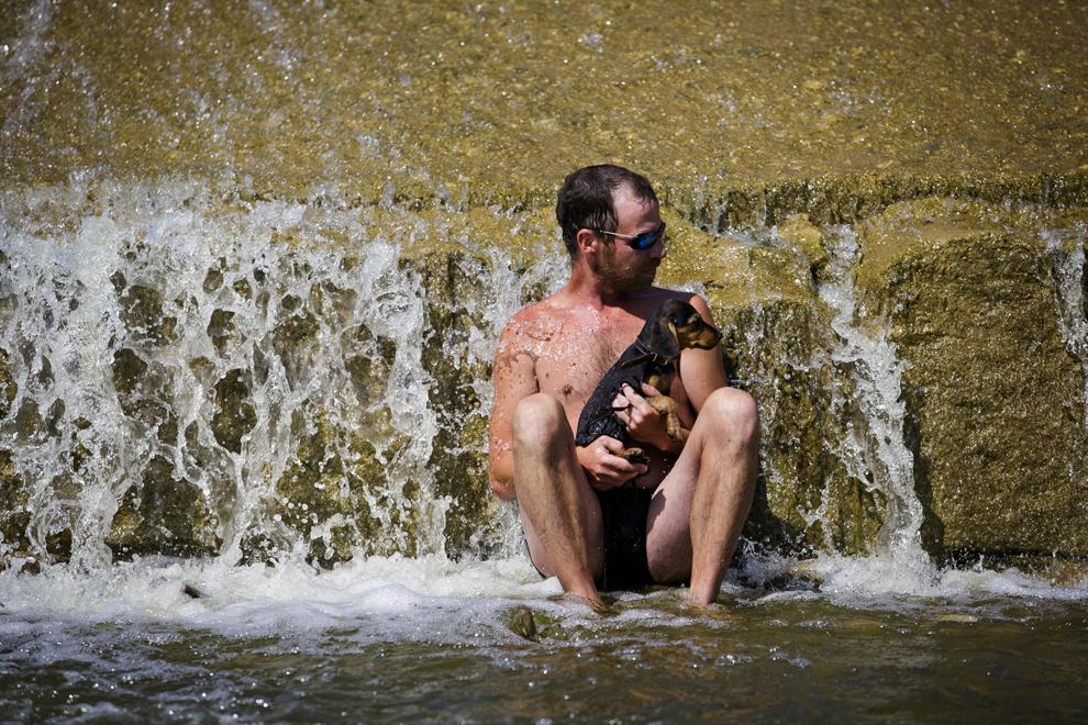 Un tânăr se relaxează la barajul râului Berounka, în apropiere de Dobrichovice, Cehia, duminică, 28 iulie 2013.