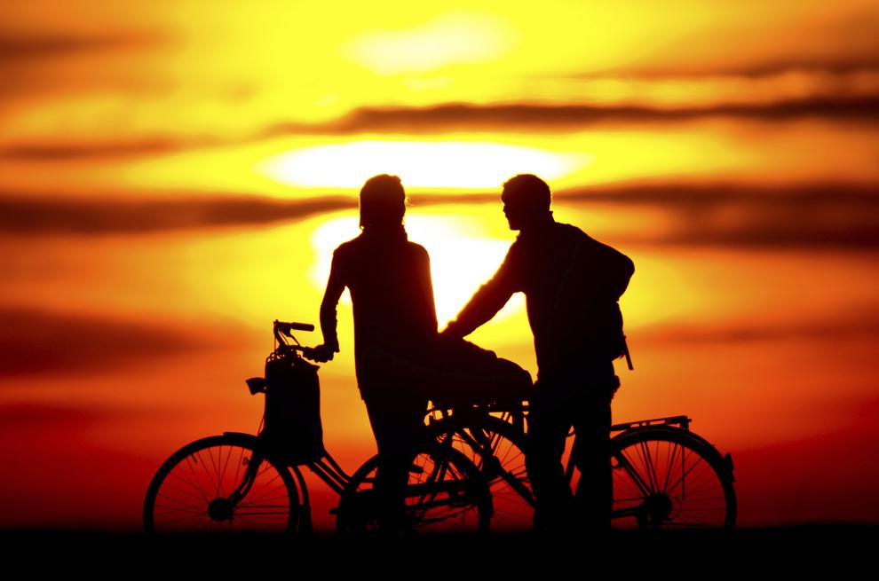 Doi ciclişti admiră apusul soarelui, în Berlin, Germania, joi, 20 martie 2014.