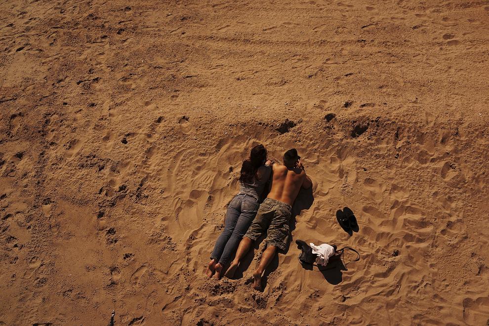Doi tineri stau la plajă în Coney Island, New York, sâmbătă, 12 aprilie 2014.