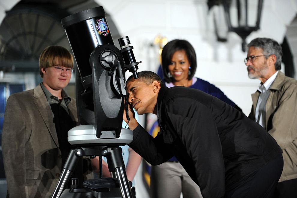 Preşedintele SUA, Barack Obama, priveşte printr-un telescop în timpul unui eveniment de astronomie organizat pentru elevii de gimnaziu, pe peluza de Sud a Casei Albe, în Washington, D.C., miercuri, 7 octombrie 2009. (Tim Sloan / AFP)
