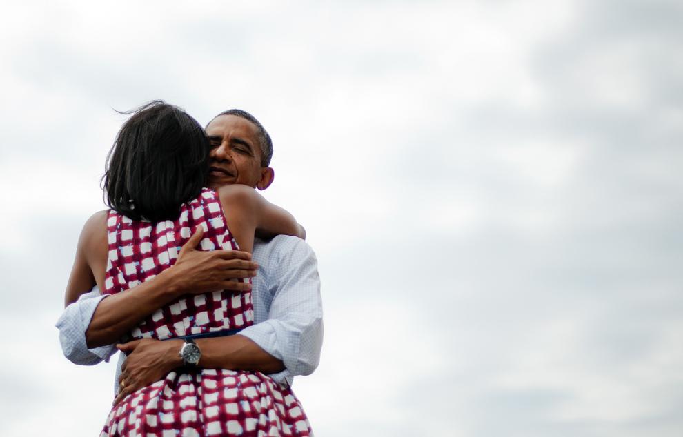 Prima Doamna Michelle Obama (S) il îmbrăţişează pe Preşedintele Statelor Unite ale Americii, Barack Obama la finalul unui eveniment de campanie la Alliant Energy Amphitheater, în Dubuque, Iowa, miercuri, 15 august 2012. (Jim Watson / AFP)