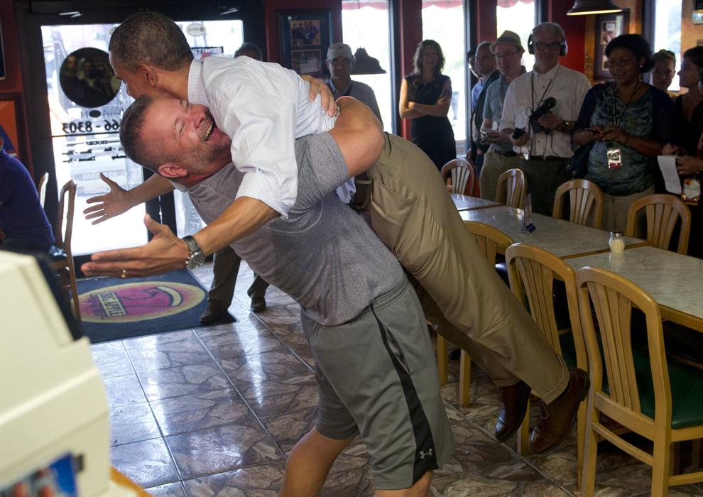 Preşedintele Statelor Unite ale Americii, Barack Obama este îmbrăţişat de către propietarul restaurantului italian Big Apple Pizza and Pasta, Scott Van Duzer, în timpul unei vizite în Fort Pierce, Florida, duminică, 9 septembrie 2012. (Saul Loeb / AFP)