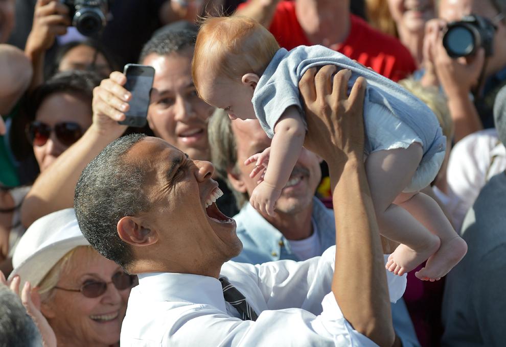 Preşedintele SUA Barack Obama ţine în braţe un copil, în timpul unei campanii electorale, în Cheyenne Sports Complex, în Las Vegas, Nevada, joi, 1 Noiembrie 2012. (Jewel Samad / AFP)