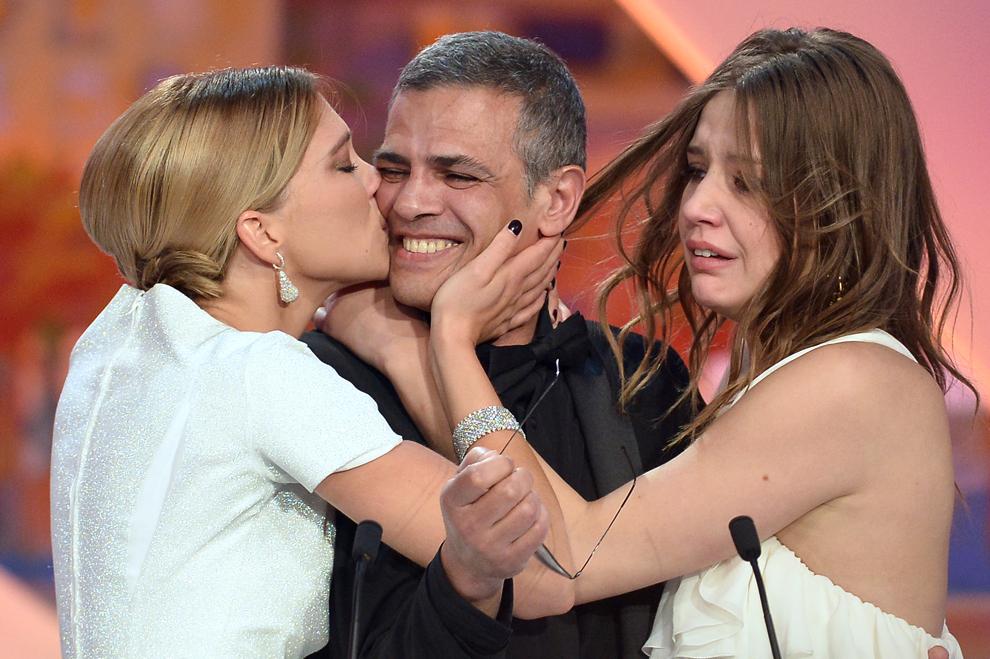 Actriţa franceză Lea Seydoux (S) îl sărută pe regizorul franco-tunisian Abdellatif Kechiche (C), lângă actriţa Adele Exarchopoulos, după ce acesta a primit premiul Palme D'Or pentru filmul 'Blue is the Warmest Colour', în timpul ceremoniei de închidere a celei de-a 66-a ediţii a Festivalului de Film de la Cannes, în Cannes, duminică, 26 mai 2013.