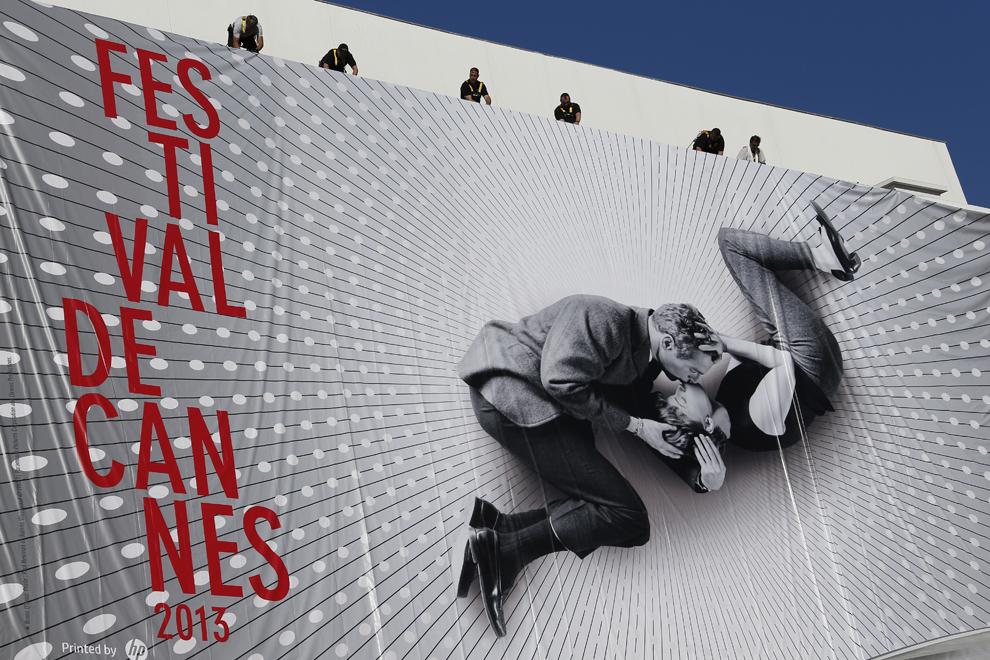 Mai mulţi muncitori desfăşoară un poster gigant al celei de-a 66-a ediţii a Festivalului de Film de la Cannes care reproduce o fotografie veche de 50 de ani ce îi înfăţişează pe actorii Paul Newman şi Joanne Woodward sărutându-se, în Cannes, luni, 13 mai 2013.