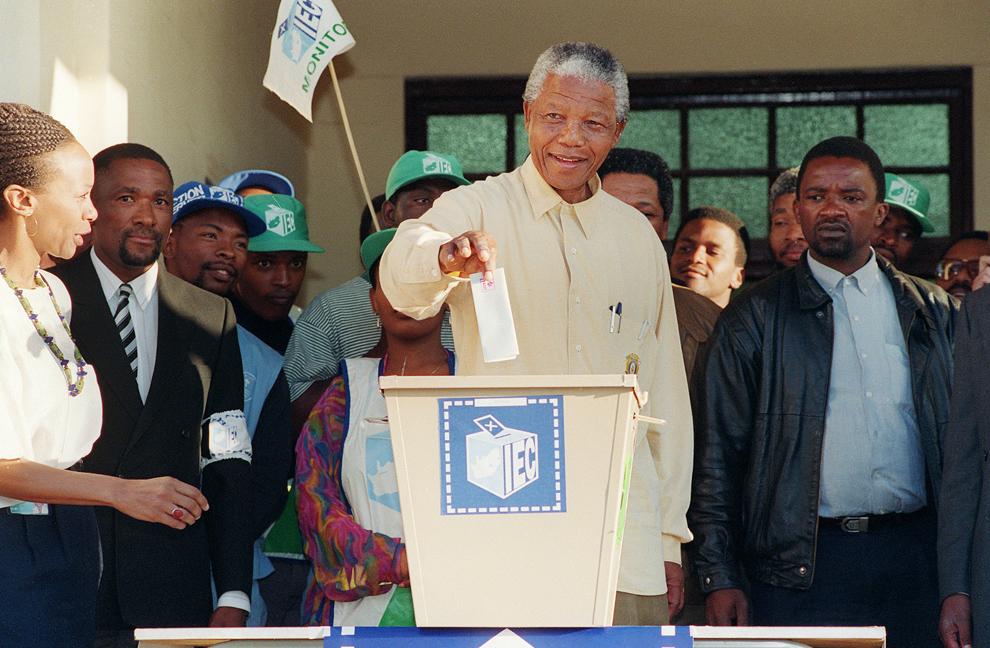 Preşedintele Congresului Naţional African (CNA), Nelson Mandela, zâmbeşte în timp ce introduce în urnă buletinul de vot, cu ocazia primelor alegeri generale democratice şi multirasiale, în ghetoul Oshlange de lângă Durban, miercuri, 27 aprilie 1994.