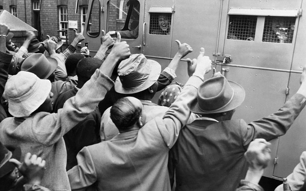 Suporteri ai Congresului Naţional African (CNA) îi încurajează pe militanţii anti-apartheid care sunt duşi cu o dubă la tribunalul din Johannesburg, vineri, 28 decembrie 1956. 152 de militanţi anti-apartheid, printre care şi Nelson Mandela, sunt judecaţi la Johannesburg.