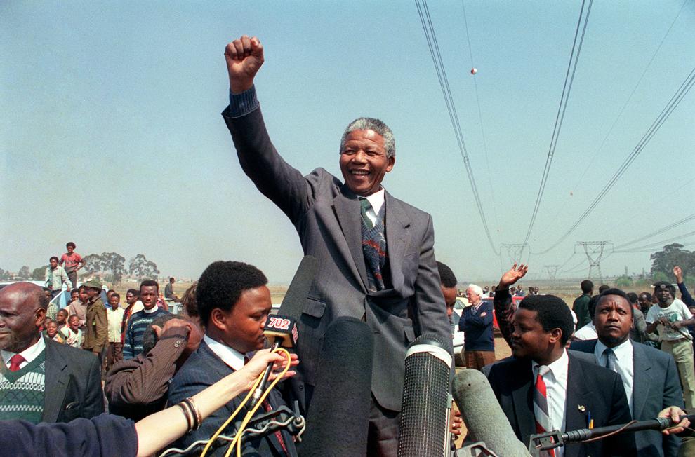 Liderul anti-apartheid şi membru al Congresului Naţional African (CNA), Nelson Mandela, ridică pumnul în timp ce se adresează locuitorilor taberei din parcul Phola, în Tokoza, în timpul turului ghetourilor sud-africane, miercuri, 5 septembrie 1990.