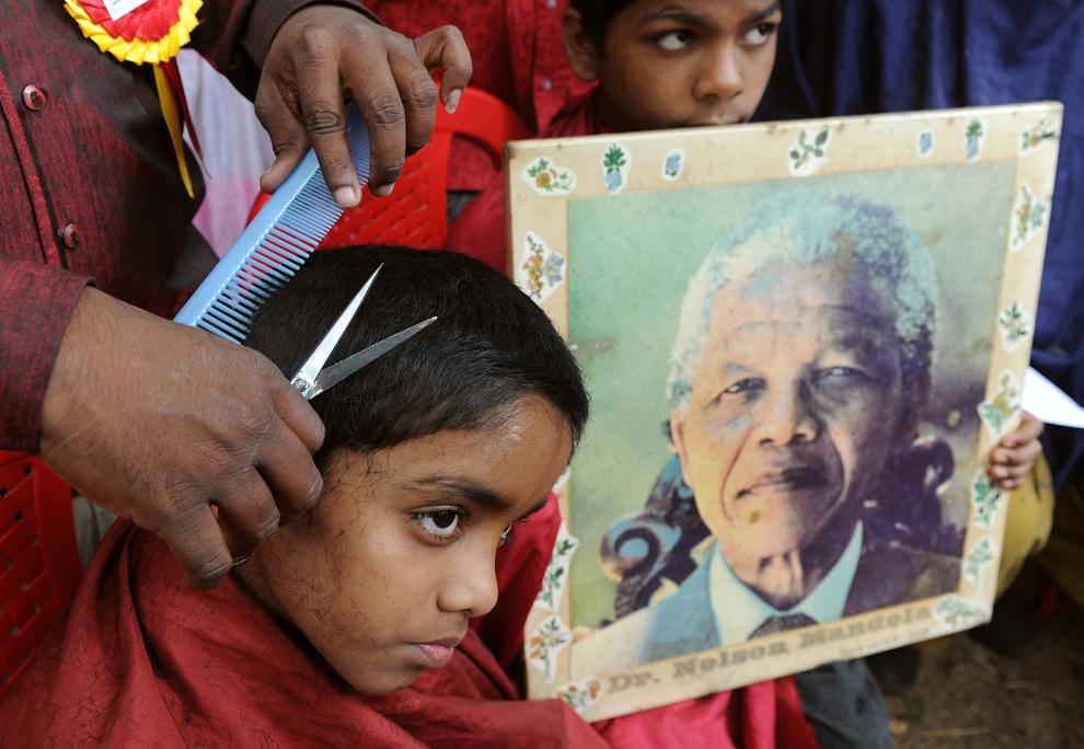 Un copil sărac (S) primeşte gratis o tunsoare din partea membrilor Forumului Fanilor Dr. Nelson Mandela, în timp ce alt copil pozează cu un portret al lui Mandela, în Bangalore, luni, 18 iulie 2011. Evenimentul caritabil  a fost organizat în onoarea celei de-a 93-a aniversări a fostului preşedinte sud-african şi lider anti-apartheid, Nelson Mandela.