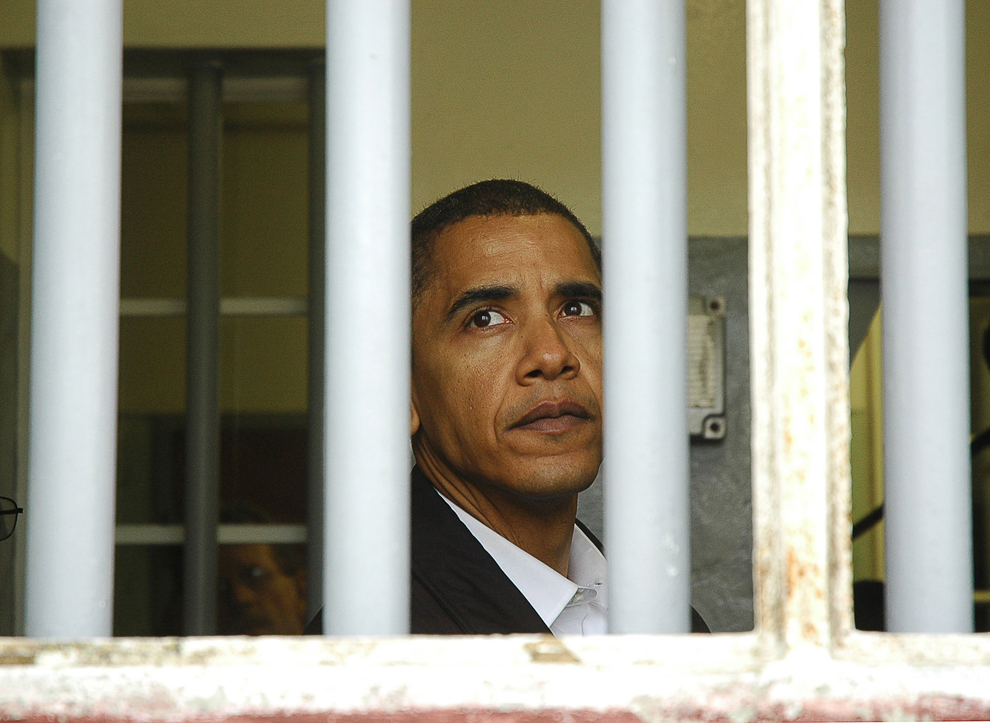 Senatorul american de Illinois, Barack Obama, priveşte pe fereastra celulei în care Nelson Mandela a fost încarcerat timp de 18 ani, pe insula Robben, la 6 km de Cape Town, în golful Table, duminică, 20 august 2006.