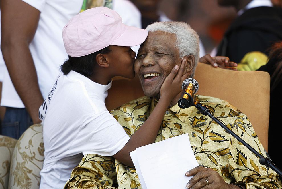 Fostul preşedinte sud-african Nelson Mandela râde în timp ce este pupat de o nepoată, după ce a susţinut un discurs în cadrul evenimentului organizat de Congresul Naţional African (CNA),  pe stadionul Loftus din Pretoria, pentru a sărbători cea de-a 90-a aniversare a zilei sale de naştere, sâmbătă, 2 august 2008.