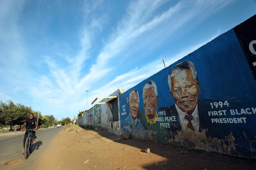 Un copil, aflat pe bicicletă, trece pe lângă un zid acoperit cu potrete ale fostului preşedinte sud-african, Nelson Mandela, în Soweto, vineri, 29 martie 2013.
