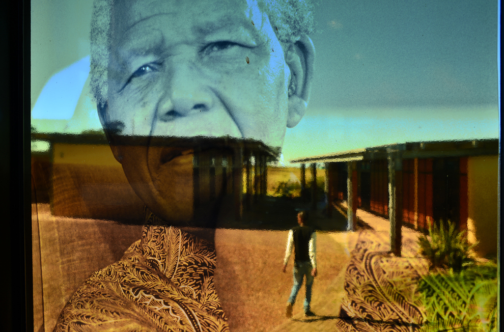 Un bărbat trece prin faţa unei ferestre transparente, pe care se află o imagine a fostului preşedinte sud-african, Nelson Mandela, la muzeul Nelson Mandela din Qunu, în Africa de Sud, vineri, 5 aprilie 2013.